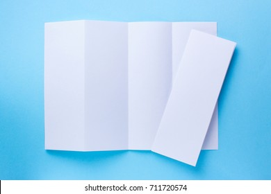 Leaflet blank Four-fold white paper brochure mockup on blue background. top view
