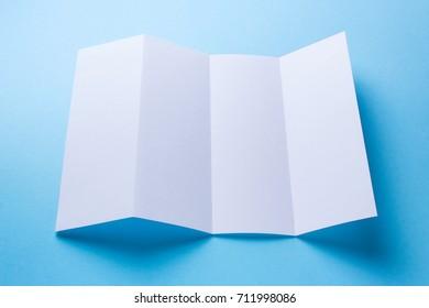 Leaflet blank Four-fold white paper brochure mockup on blue background