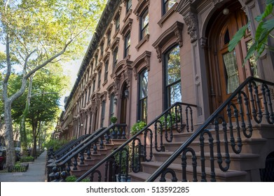 Leafy summer view of the row of stoops on one of the iconic streets of the neighborhood of Brownstone Brooklyn in New York City