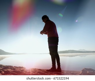 Leakage of light in the lens. Damaged photo effect. Tall slim  man exercise   on the mountain lake beach. Silhouette against to Sun.