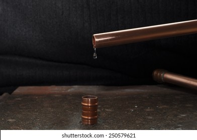 Leaking Pipe, plumbing materials with a drip coming from a copper pipe on a slate with a soft black background.