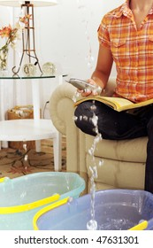 Leaking roof or pipe burst: woman calling insurance or plumber
