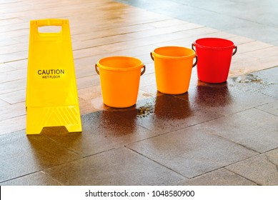 From the leaky roof, the water drips onto the floor.Water drips into the bucket and onto the floor. A slippery wet floor marked with a safety poster.