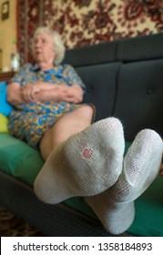 Leaky sock. Elderly woman sitting on the sofa