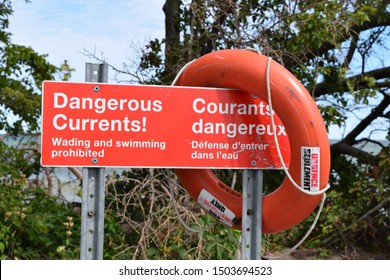 Leamington, ON - September 2019: Dangerous current sign with red lifeline. Safety warning. No swimming. Wading prohibited. Emergency only. Bilingual French English red sign. Lifesaver.