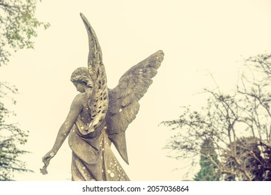 Leamington Spa, Warwickshire  UK - 10 10 2021: Angel seen from behind, guiding the soul to heaven. Sculpture in a cemetery. Spiritual peace.