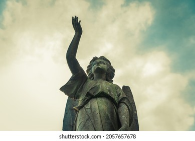Leamington Spa, Warwickshire, UK - 10 10 2021: Angel with arm up, guiding the soul to heaven. Sculpture in a cemetery. Spiritual peace.