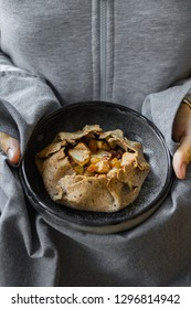 Lean crispy baked cake or pie with apples, pumpkin, honey, cinnamon and bananas. Woman hands holds healthy vegan dessert