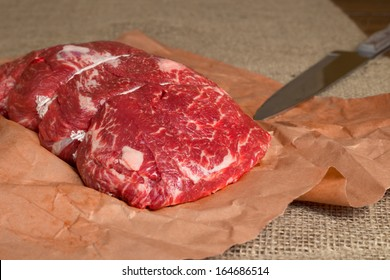 Lean cut of raw beef on butcher paper with knife