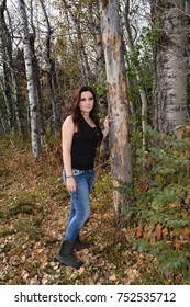 Leaning up against a tree - young woman wearing a black tank top with long dark hair