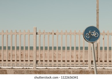Leaning bike traffic signal and railway fence background (Pesaro, Italy)