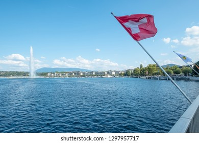 Leaning diagonally into the photo over Lake Geneva, a bright red flag with iconic white cross flies over a background including Geneva's waterfront and the iconic Jet d'eau