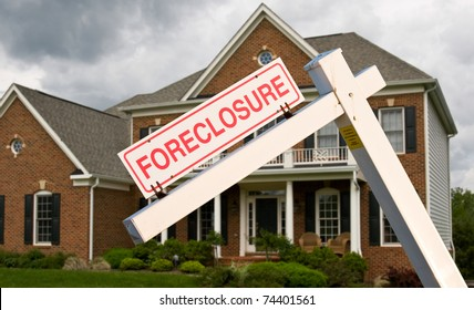 Leaning foreclosure sign in front of a modern single family home on a cloudy cold day