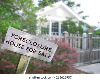 Leaning home for sale real estate and foreclosure sign in front of a modern single family home.