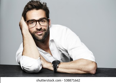 Leaning man in glasses and white shirt, portrait