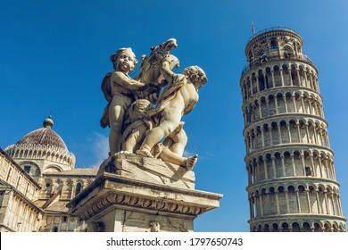 Der legende Turm von Pisa und Kathedrale am Tag. Statue mit Engeln im Vordergrund. Große Feldtiefe.