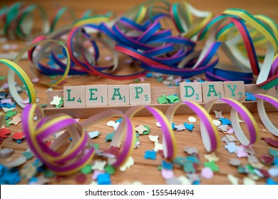 Leap day spelled in scrabble tiles, surrounded with festive confetti and guirlandes. Placed on wooden underground. Leap day is only once every four years on February 29th.