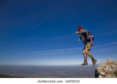 Leap of faith - A mountaineer jumping trough the rocks, over a clear blue sky