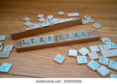 Leap year spelled in Scrabble blocks, surrounded with random scrabble blocks. Placed on wooden underground. Leap year only occurs every four years, leap day is February 29.