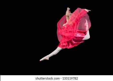 Leaping ballerina studio portrait against black