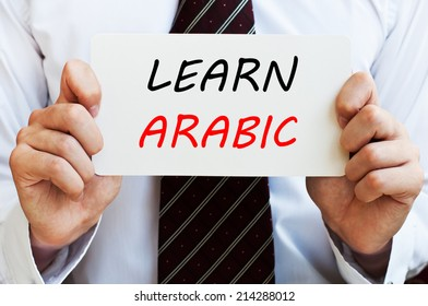 Learn Arabic - man wearing a shirt and a tie holding a signboard with a text on it. Education concept.