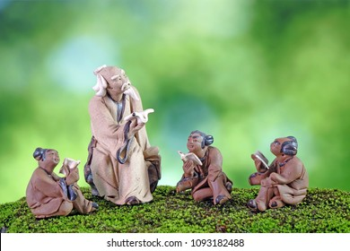 Learn Chinese language concepts : Clay sculptures of Confucius with students reading book. Selective focus, blurred background with copy space