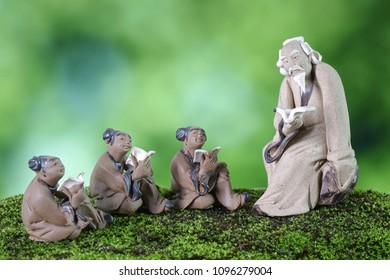 Learn Chinese language concepts : Clay sculptures of Confucius with students reading book. Selective focus, blurred background with copy space.