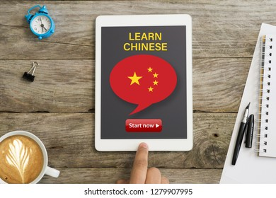 Learn Chinese language through online webinar or course with white tablet on wooden desk