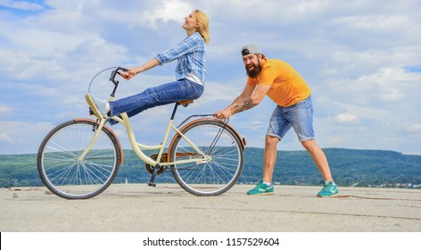 Learn cycling with support. Cycling technique. Woman rides bicycle sky background. Man helps keep balance and ride bike. How to learn to ride bike as adult. Girl cycling while boyfriend support her.