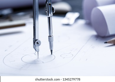 Learn to draw circles with a compass. Compasses and Architect scale ruler placed on the desk, filled with building plans. industrial drawing detail and several drawing tools. selective focus