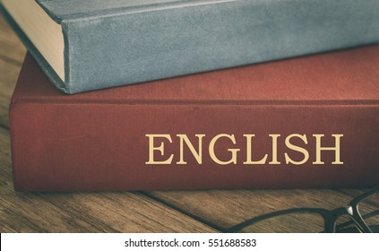 Learn English concept, Old English textbooks, antiquarian books pile on wood table.