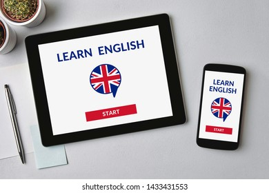 Learn English concept on tablet and smartphone screen over gray table. Flat lay