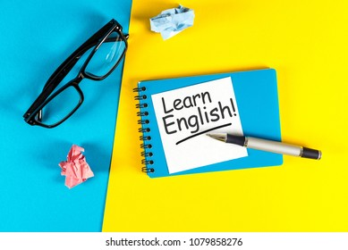 Learn english - note at blue and yellow background with teachers glasses