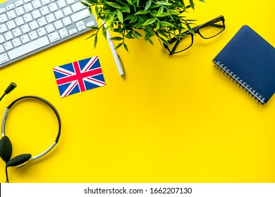 Learn English online. Concept with british flag, headset and keyboard on yellow background top-down copyt space
