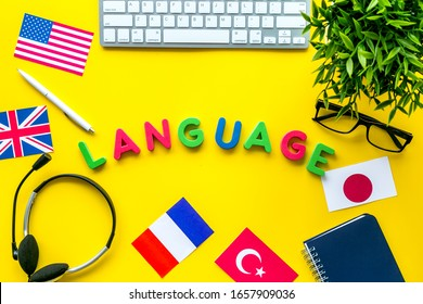Learn foreign language online. Concept with text, headset and keyboard on yellow background top-down