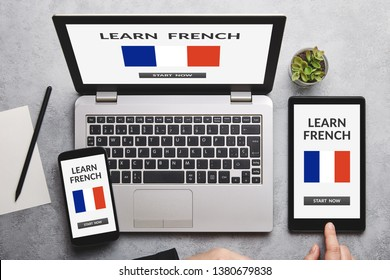 Learn French concept on laptop, tablet and smartphone screen over gray table.  Flat lay