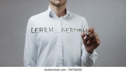 Learn german , Man Writing on Glass