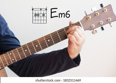 Learn Guitar - Man in a dark blue shirt playing guitar chords displayed on whiteboard, Chord E Minor 6