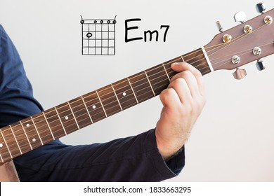 Learn Guitar - Man in a dark blue shirt playing guitar chords displayed on whiteboard, Chord E minor 7