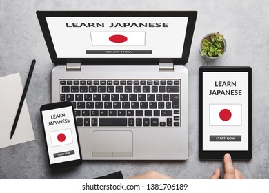 Learn Japanese concept on laptop, tablet and smartphone screen over gray table. Flat lay