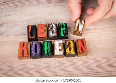 LEARN KOREAN. Language training, skills and education concept. Colored wooden letters on a light background