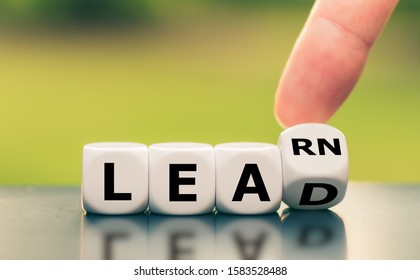 """Learn and Lead. Hand turns a dice and changes the word """"learn"""" to """"lead""""."""