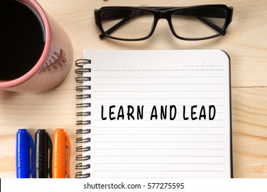 Learn And Lead on notebook with cup of coffee and glasses on wooden background.