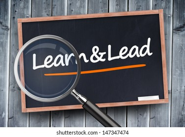 Learn and lead written on a blackboard with magnifying glass