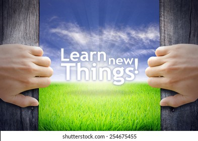 """""""Learn new Things"""" Motivational quotes. Hands opening a wooden door then found a texts floating among new world as green grass field, Blue sky and the Sunrise."""