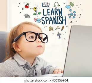 Learn Spanish concept with toddler girl using her laptop