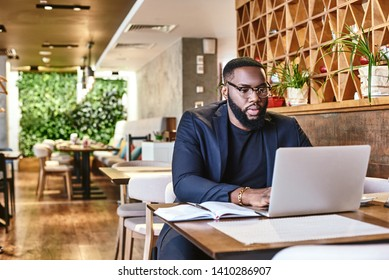 I learned the value of hard work by working hard. African american businessman is working, using his laptop while resting in the cafe