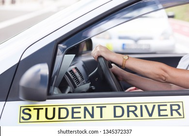 Learner driver holding steering wheel during driving lesson