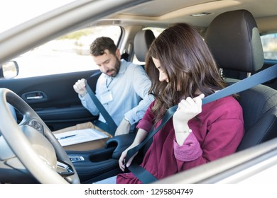 Learner and mid adult driver fastening seatbelts while sitting in car