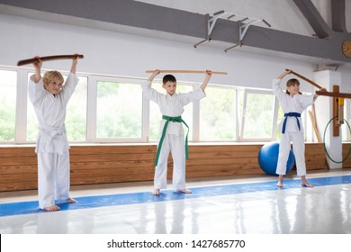 Learning aikido. Two boys and one girl wearing uniform feeling curious while learning aikido movements
